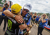 Mar 20, 2016; Gainesville, FL, USA; NHRA top fuel driver Brittany Force (left) is embraced by her father John Force (center) as sister Courtney Force cries as they celebrate after winning the Gatornationals at Auto Plus Raceway at Gainesville. Mandatory Credit: Mark J. Rebilas-USA TODAY Sports