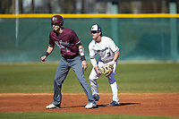 Wingate Bulldogs shortstop Carson Simpson (3) checks Concord Mountain Lions runner Anthony Stehlin (12) at Ron Christopher Stadium on February 2, 2020 in Wingate, North Carolina. The Mountain Lions defeated the Bulldogs 12-11. (Brian Westerholt/Four Seam Images)