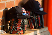 Elizabethton Twins hats sit on top of gloves in the visitors dugout at Howard Johnson Field July 3, 2010, in Johnson City, Tennessee.  Photo by Brian Westerholt / Four Seam Images