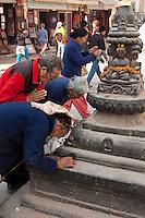 Bodhnath, Nepal.  Worshipers Pray at a Shrine at the Base of the Bodhnath Stupa, a Tibetan Buddhist Stupa.