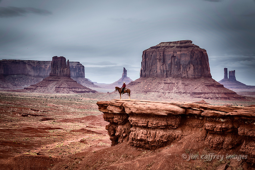 A lone rider in an iconic view of Monument Valley with Merrick Butte and the East Mitten visible in the background