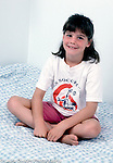 8 year old girl portrait sitting on bed vertical