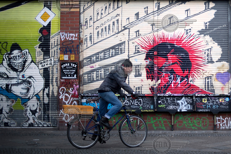 A man rides his bicycle along Oranienburger Strasse, past graffiti covered walls in Kreuzberg, a district undergoing significant redevelopment and gentrification.