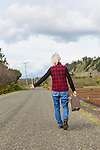 Senior woman with suitcase walks a back road amid cranberry farms.  Near Graylend Beach, State Park, Tokeland Beach, on the central Washington Paciific Coast south of Westport, is flooded by rain making for an unusual landscape of water in the sand dunes.