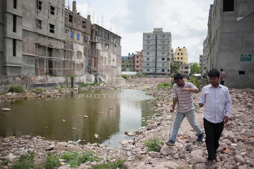 Rhedoy, a victim of Rana Plaza collapse, walks with another victim beside the Rana Plaza collapse site in Savar, near Dhaka, Bangladesh