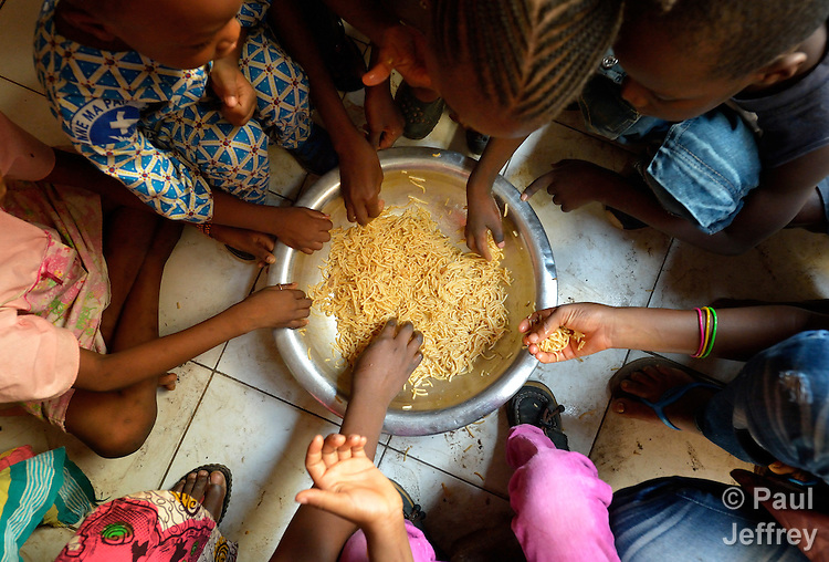 Displaced children eat a meal in a house shared by several internally displaced families in Bamako, Mali. Thousands of families displaced by the fighting in northern Mali have taken refuge in the capital and other areas of the country's south, most living with relatives or renting small spaces. Many have received support from the ACT Alliance.