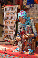 Morocco.  Young Amazigh Berber Girl Working with Wool on a Spindle.  Ait Benhaddou Ksar, a World Heritage Site.