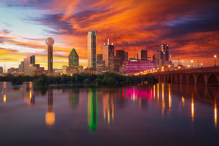 """""""Dallas Skyline at Dusk"""" - Illuminated by a blend of ambient and artificial light, sunset radiates off the Dallas skyline as the city is reflected back in the flooded Trinity River. As the sun prepares to dip below the horizon, Bank of America Plaza (centered) glows neon green while lights on the iconic Reunion Tower (far left) flash and sparkle, bringing the city to life as the night quickly approaches."""