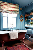 A free-standing roll-topped bath has been painted a deep red, contrasting with the eggshell blue tongue and groove walls