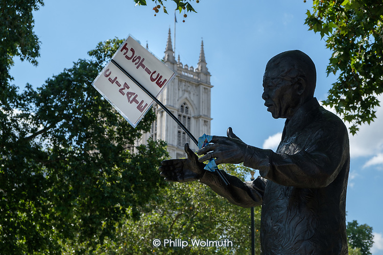 Statue of Nelson Mandela, with Climate Justice placard.  Extinction Rebellion protest, Parliament Square, London