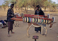 Akadaney, Central Niger, West Africa.  Fulani Nomads.  Women Loading Portable Bed Pieces on Donkey.