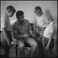 Août 1959. Vue de René Pleimelding, entraîneur du Toulouse Football Club, montrant un trophée à ses enfants.