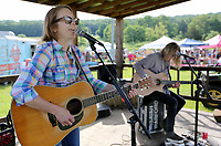 Sarah Hughes (left) and Isayah Warford play a song Friday, June 4, 2021, from her new compact disc Memphis during the Junk Ranch Spring Show in Prairie Grove. The show continues today featuring vintage, antique, handmade, repurposed, jewelry, boutique, and salvage items with food trucks and live music. Check out nwaonline.com/210605Daily/ and nwadg.com/photos for a photo gallery.<br /> (NWA Democrat-Gazette/David Gottschalk)