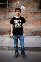 Liangyong, no occupation given, age 25, poses for a portrait in Beijing. Response to 'What does China mean to you?': 'Nation, mother, a lot of passion.'  Response to 'What is your role in China's future?': 'Grand.'