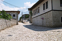 Street scene up towards the centre of the village from the entrance gate with old houses. Berat upper citadel old walled city. Albania, Balkan, Europe.