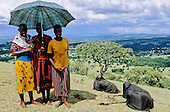 Lolgorian, Kenya. Siria Maasai; newly circumscised girls wrapped in black recovering on a hillside with three women.