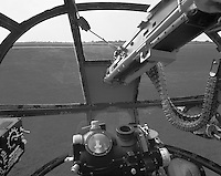 """""""Bombardier's View in a B-25"""" <br /> 2012 Salute to Veterans Airshow, Columbia, Missouri <br /> <br /> This photograph shows the bombardier's view in a B-25 """"Mitchell"""" bomber. The B-25 began service early in World War II as a medium bomber and soon proved to be effective for strafing because of the number of its forward firing guns. The B-25 became well known when it was used for the famous Doolittle raid into Japan soon after the bombing of Pearl Harbor. The famous Nordon bombsight is at the bottom center and a bomb """"train"""" control box is at the lower left. The bombardier's 50 caliber machine gun enters the photo from the upper right and barrels of two 50 caliber machine guns that were fired by the pilots can be seen at the lower right and bottom right. The airplane was piloted by Greg Vallero and photographed at the 2012 Memorial Day Weekend """"Salute to Veterans"""" airshow in Columbia, Missouri."""