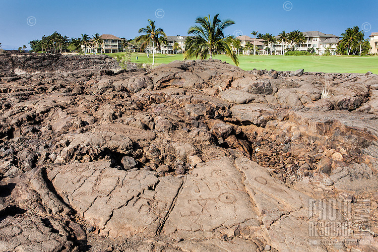 Petroglyphs or ki'i pohaku in front of the King's Course golf course and condos at the Waikoloa Petroglyph Field (a.k.a. 'Anaeho'omalu Petroglyph Field), Big Island.