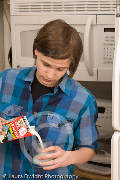 Teenage boy at home in kitchen pouring self glass of milk Caucasian vertical age 14