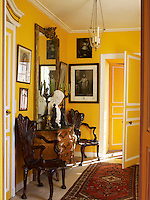 An 18th century chest of drawers stands underneath a gilt-framed mirror in one of the hallways, flanked by two elaborately carved chairs