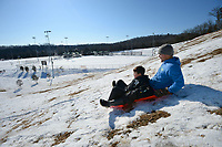 Austin Sutton (right) of Fayetteville and his son, Titan Sutton, 8, ride downhill Saturday, Feb. 20, 2021, near ball fields while sledding at Kessler Mountain Regional Park in Fayetteville. The Fayetteville City Council on Thursday approved a nearly $6.4 million construction contract to build a second four-field baseball complex at the park. Visit nwaonline.com/210221Daily/ for today's photo gallery. <br /> (NWA Democrat-Gazette/Andy Shupe)