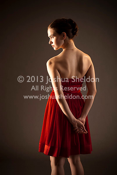 Young woman wearing red dress with arms in back of her