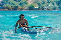 Tahitian man paddling in traditional Polynesian outrigger canoe on turquoise Bora Bora island lagoon, near Tahiti, French Polynesia, Pacific Ocean