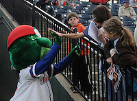 Mascot Reedy Rip'It of the Greenville Drive high-fives a fan prior to a game against the Lakewood BlueClaws on Opening Day, April 5, 2012, at Fluor Field at the West End in Greenville, South Carolina. (Tom Priddy/Four Seam Images)