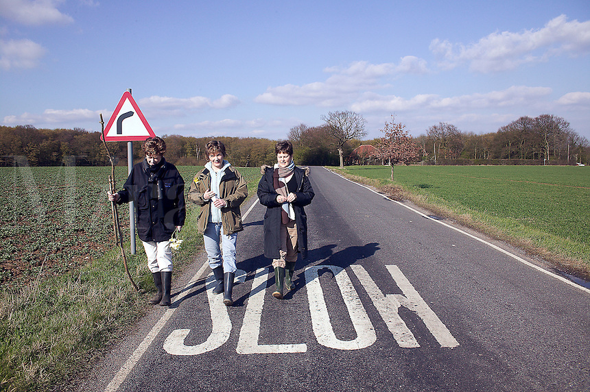 Mother and two daughters walk in Essex Great Britain country lane...(R