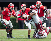 ATHENS, GA - OCTOBER 12: Jake Fromm #11 of the Georgia Bulldogs is tackled by D.J. Wonnum #8 of the South Carolina Gamecocks during a game between University of South Carolina Gamecocks and University of Georgia Bulldogs at Sanford Stadium on October 12, 2019 in Athens, Georgia.