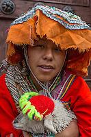 Peru, Cusco.  Young Quechua Girl in Traditional Dress, Holding Pet Lamb.