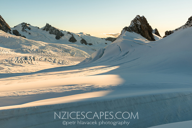Sun sets over mountain ranges of Southern Alps and crevasses in upper parts of Fox Glacier NEVE, Westland Tai Poutini National Park, West Coast, UNESCO World Heritage Area, New Zealand, NZ