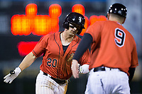Tate Blackman (20) of the Kannapolis Intimidators prepares to shake hands with Kannapolis Intimidators manager Justin Jirschele (9) as he rounds third base after hitting a home run against the Lakewood BlueClaws at Kannapolis Intimidators Stadium on April 6, 2018 in Kannapolis, North Carolina.  The BlueClaws defeated the Intimidators 4-3.  (Brian Westerholt/Four Seam Images)