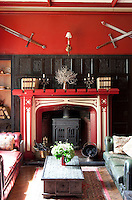A harlequin-inspired fireplace with a wood burning stove set against decorative wood panelling.