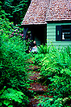 Woman rests on porch of cabin in forested countryside of Washington State.  Native plants blooming and growning over the walkway, which leads to inviting porch and lemonade.