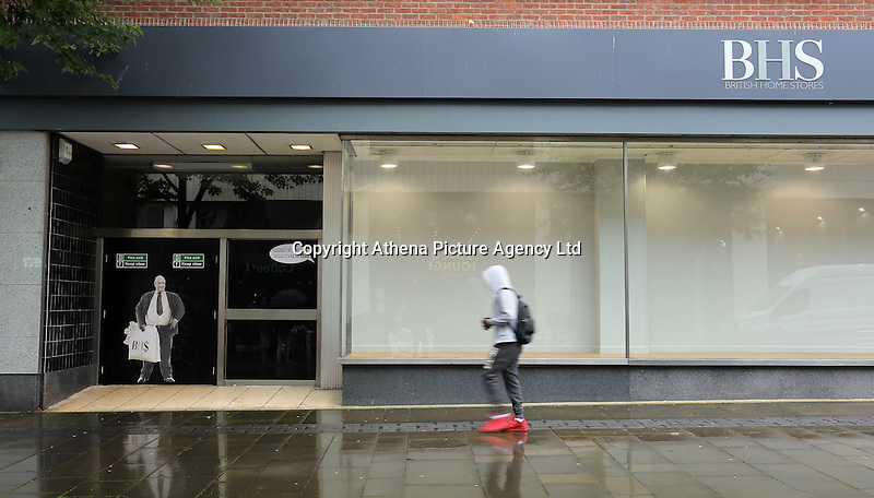 """Pictured: A man walks past a poster of Sir Philip Green on the door of the now closed down BHS store in Oxford Street, Swansea, Wales, UK. Tuesday 13 September 2016<br /> Re: Former owner of BHS, Sir Philip Green has paid a surprise 'visit' to the closed down BHS store in Swansea.<br /> He was spotted in the doorway of the Oxford Street store, which closed its doors for the last time last month.<br /> In his hand was a BHS shopping bag with money spilling out of it.<br /> Sir Philip had owned BHS before selling it for £1 last year.<br /> He is claimed to have taken millions out of the company in dividends and left behind a £571m pensions deficit.<br /> Alongside the poster are the words: """"Thankyou for your custom Sir""""."""