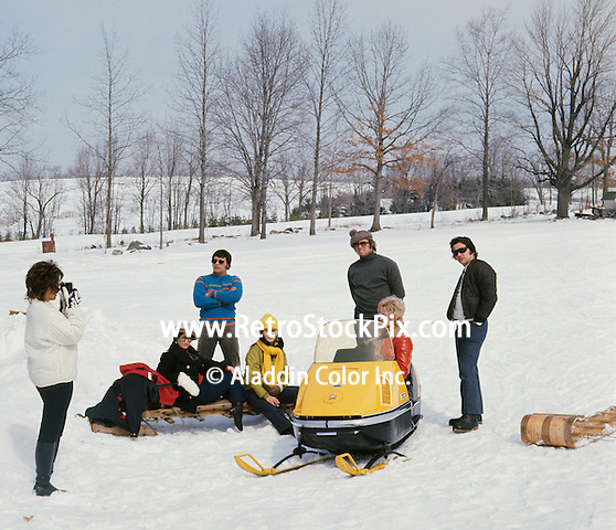 Woman clicking photograph of friends standing by snowmobile