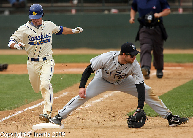 SIOUX FALLS, SD - MAY 17: Joe Anthonen #4 of the Sioux Falls Canaries steps safely on first as first baseman Ole Sheldon #23 of the St. Paul Saints scoops the ball the eighth inning Sunday afternoon at the Sioux Falls Stadium. (Photo by Dave Eggen/Inertia).