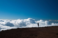 Kaleo looks over the tops of clouds from Haleakala summit, Haleakala National Park, Maui.