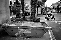 Switzerland. Canton Ticino. Lugano. Dumpster near a construction site. A young boy rides on the asphalt road a rented electrical bicycle. Palms trees in the street. Private parking place. 15.06.2020 © 2020 Didier Ruef