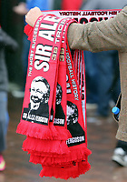 Pictured: Sir Alex Ferguson souvenir scarves sold by street vendors outside the ground before kick off. Sunday 12 May 2013<br />