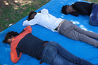 Italy. Lombardy Region. Como. Homeless african migrants living in the park below the San Giovanni railway station. Three Eritrean men are sleeping in the afernoon lying on a blue blanket on the ground. 10.08.2016 © 2016 Didier Ruef