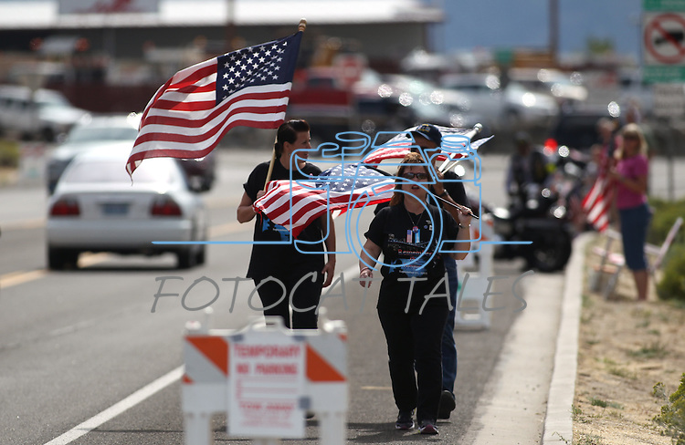 About 400 people rallied outside the Nevada National Guard facility in Carson City Nev., on Sunday, Sept. 11, 2011, during a private memorial to honor three Guard members killed earlier this week by a gunman in an IHOP restaurant. (AP Photo/Cathleen Allison)