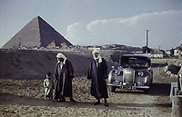 A Dutch student in local dress with a guide and his little son, near the pyramid of Cheops (Khufu) with its annexes (?). Electricity poles and power cables. A  car,possibly a BENTLEY, 6 November 1961