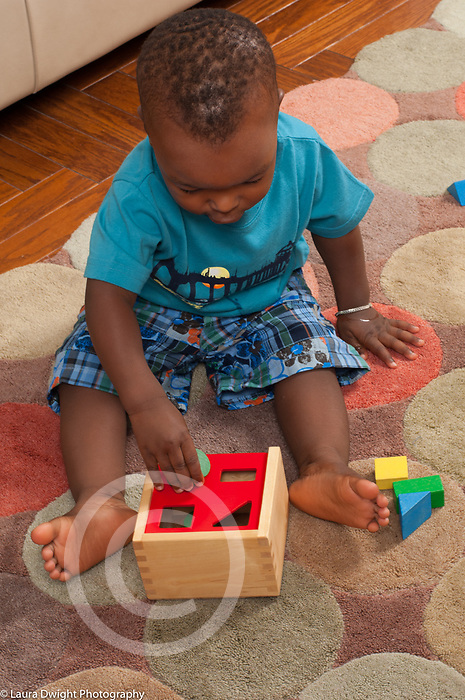 15 month old toddler baby boy playing with shape sorter toy vertical
