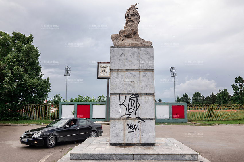 Albania. Korçë.  A black Mercedes drives by a Skanderbeg statue. Graffiti on the granite stone. George Castriot (Albanian: Gjergj Kastrioti, 6 May 1405 – 17 January 1468), known as Skanderbeg was an Albanian nobleman and military commander, who led a rebellion against the Ottoman Empire in what is today Albania. Skanderbeg always signed himself as Lord of Albania (Latin: Dominus Albaniae), and claimed no other titles but that in official documents. Klubi Futbollistik Skënderbeu Korçë is an Albanian professional football club based which plays in the Albanian Superliga, The club's name is Skënderbeu Korçë, after Albania's national hero Skanderbeg. The club's home ground has been the Skënderbeu Stadium since it was built in 1957, and it now has a capacity of 12,343. Korçë is a city and municipality in southeastern Albania. 21.05.2018  © 2018 Didier Ruef