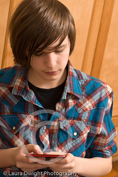 Teenage boy 14 years old closeup texting on cell telephone vertical Caucasian text messaging