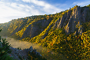 Morning sun bounces off the cliffs in Dixville Notch State Park in New Hampshire USA from a scenic viewpoint along the Sanguinary Ridge Trail during the autumn months. Fog can also be seen in the scene.