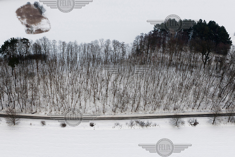 Snow covered hills and fields at Kostrzyn as a road runs past the frozen Odra River.