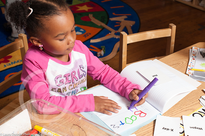 Education preschool 3-4 year olds girl sitting writing words using marker. She is using her left hand